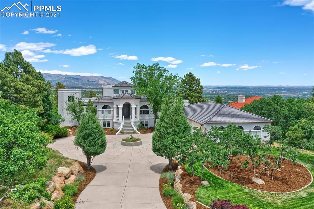 Stunning Contemporary resort-style custom home with magnificent Views of Cheyenne Mtn, Front Range, Broadmoor, Garden/Gods, Downtown, Gates CC, city lights & beyond. Your work from home total resort! French doors open to 2K sq ft of custom decks. Quiet private lot backs to open space, scrub oak, mature trees, and wildlife. Complete privacy from neighbors in a gated community. Brand new mechanical, appliances, flooring, exterior, multiple office spaces, gourmet Kitchen, indoor pool, Gym,  indoor/outdoor floorplan flows from views on every level to the fresh, breathtaking outdoor spaces on a perfect lot. Ideal for entertaining or family time, dramatic Entry, vaulted ceiling main floor, natural beams & wood ceilings in LR, DR & Kitchen. The Master suite is a true 1200+ sq ft sanctuary & retreat, wake-up to the sun rising from bed, elegant gas fireplace, curved sitting area with views, Marble showcase Bath, rounded walk-in pool glass shower w/heated floor & bench, Victoria Albert tub, heated floors, suspended dual vanities, his/her walk-in closets, sitting area, circular staircase to private 360 Turret Office w/separate heat/AC & roof access to private roof top with world class views of stunning Colorado!  All beautiful rich hardwood, marble & tile in the entire home with no carpeting. Plenty of room for every vehicle, toy & tool in completely/professionally finished 4+ Car Garage, epoxy floor, heated workshop area. Mud room with sunny bright Laundry, deck access & views. Lower-level w/2 ensuite Bedrms + Bedrm/Bath suite, Family room, spacious Recreation/yoga/bonus room. Architectural gem, spiral/circular staircase, art niches, arches, columns, ample storage, server room. Escape from your zoom meetings with an invigorating workout in the private exercise room, swim in the luxurious pool & relax with the sounds of the waterfall fountain, shower up a few feet away to get ready for the rest of the day/evening enjoying the city lights, a glass of wine or a gourmet dinner.