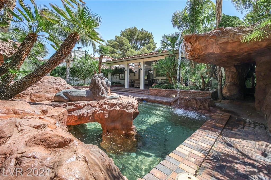 """*WOW FACTOR EXTREME*NEW LISTING*GUARD-GATED*SPANISH OAKS*ALL SOLAR PAID $45K CASH TO INSTALL*ELEC NOW $16 MNTHLY INCL A/C*(WAS $450)*LAVISH*NEWLY CUSTOMISED*PHENOMENAL *MAGICAL *PRIV YARD*SPECTACULAR HGE RED-ROCK LAGOON SWIMMING POOL*BIG GUSHING WATERFALLS*CAVE GROTTO SPA (COST $150 K)*SURROUNDED BY LUSH GREENERY*SCARY LIFE-SIZE ROCK LION & CROCODILE PERCHED ON ROCKS*MEZMERIZING TROPICAL PARADISE YOU'LL NEVER WANNA LEAVE *FORMER OWNER FAMOUS VEGAS COMEDY HEADLINER (LOVED END 0F QUIET CUL-DE-SAC SECLUSION))*INTERIOR  INCREDIBLE *GIGANTIC GREAT ROOM*ETCHED GLASS WINDOWS *GLEAMING WHITE MARBLE FLRS *HI CEILINGS*KILLER CELEBRITY-CHEF-BRAN-SPANKIN OPEN KITCHEN* BIG QUARTZ ISLAND *EVERY UPSCALE FEATURE*OPENS TO  ENTERTAINING ROOMS* WHICH ALL OPEN ONTO MASSIVE COVERED BRICK 60x20 CHARMING PATIO  (CEILING FANS, SPEAKERS ,MISTERS. BAR B Q) POOL-SIDE *FOR GREAT INDOOR-OUTDOOR GET-TOGETHERS* 4 BEDRMS (SUPERB MASTER W STAIRS TO POOL)*BDRM W FULL BATH DOWN)*SPIFFY HOME-OFFICE*LIL BITTY""""STRIP"""" VU*."""