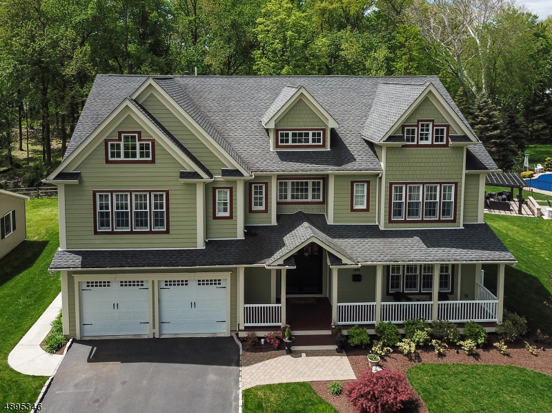 "SPECTACULAR ONE OF KIND CUSTOM COLONIAL LOADED W LUXURY UPGRADES & .2 MILES TO DIRECT NYC BUS! Welcoming front porch, dramatic 3 story foyer, gorgeous inlaid wood flrs, windows & moldings throughout, 4 levels of living space, designer baths & 9' ceilings in LR,DR,Kitch & 2nd level. Expansive chef's kitchen w massive island w seating, commercial appliances incl Thermador 36"" range & dishwasher,XO hood w make up air system,60"" refrig,wall oven,wine refrig. Family rm w 12' ceiling & stone fp. Lux master suite w sitting area, balcony & spa-like Carrara marble bath. Addit 3 bedrms have ensuite baths. Loft area w bath & potential 2 bedrms. Over 2,000 SF fin walk-out lower level w 10' ceilings & bath. Paver patio w fire pit,pergola,TV,WiFi,audio system,BBQ area. 22 KW generator. See feature sheet for more details!"