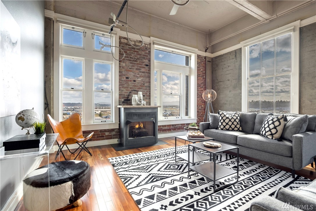 """Love luxury loft with a hint of historical, industrial, and chic?  Welcome! This upscale corner unit has views: Commencement Bay, Mt Rainier and City. Unit features: Wood floors, soaring ceilings, walls of windows, modern fixtures, open living area, chef-grade kitchen w/bar, master suite w/private, new bath and custom closets. Exclusive """"rooftop lounge"""" at the Perkins: BBQ or inspiration?  Yes! With secure entry, storage, & 2 parking spots, walk to your favorite restaurant and call this home!"""