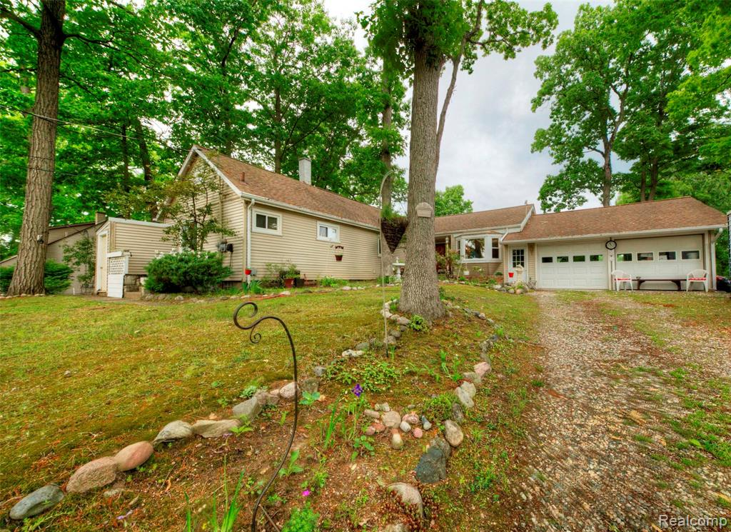 Peaceful lake living! Enjoy the serenity of Lake Handy in this large 4 bedroom, 3 full bath lakefront home with finished walkout lower level. The large main level family room features vaulted ceilings, natural brick fireplace and large doorwalls with access to rear deck and lakeviews. The kitchen has updated appliances. The large master bedroom, also with deck access, has a private full bathroom and large walk-in closet. Two more bedrooms complete the main floor. Continue to the large lower level walkout with family room and second natural fireplace with stone surround, wet bar and doorwall to the paver patio. The 4th bedroom and 3rd bath round out the lower level. Deep Lot. Main floor laundry room. Newer AC and water softener. 2 car attached garage.