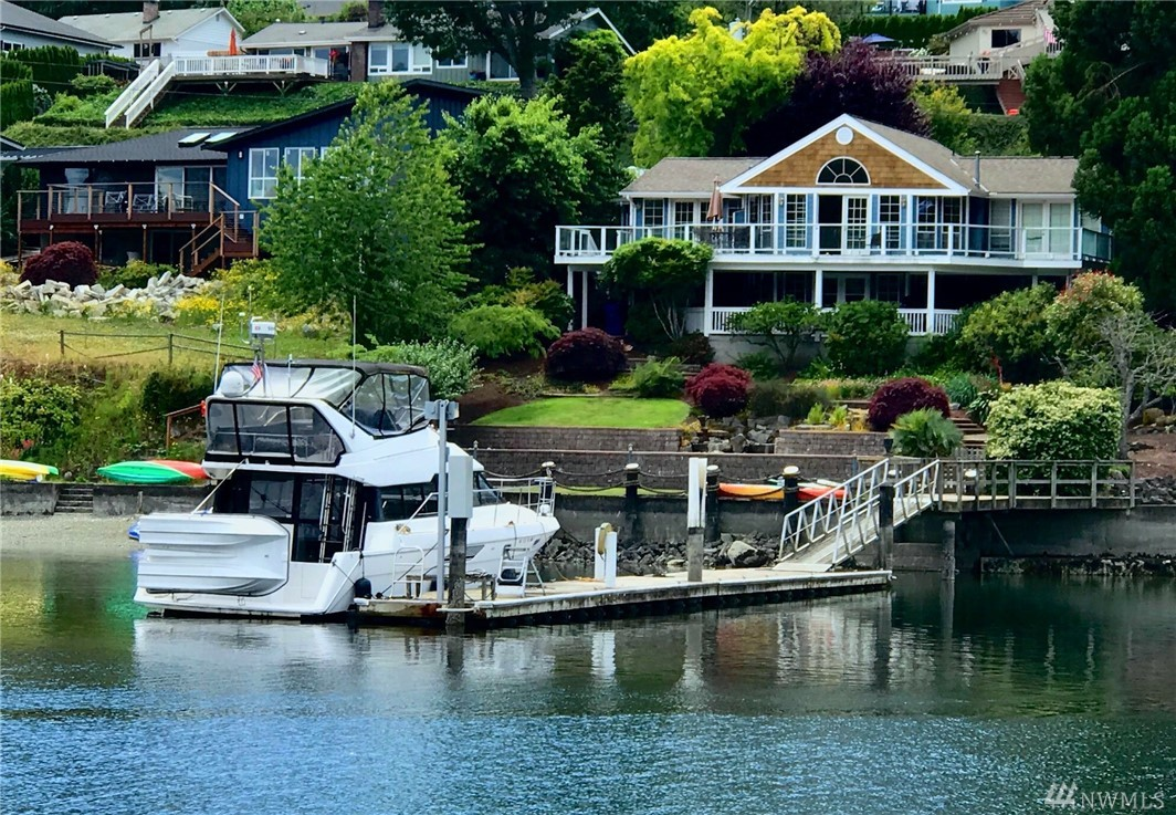 Enjoy this true waterfront retreat on Wollochet Bay w/an 80ft deep water dock – the perfect private moorage that allows your boat to be in the water at all tide levels! This 1-story home w/walk-out basement features NEW interior paint, updated kitchen w/ SS Viking appliances, hardwood floors, open living, master suite w/private bath & expansive view decks on both levels. The terraced grounds provide places to entertain all your guests & gather around the built-in fire pit during chilly nights!