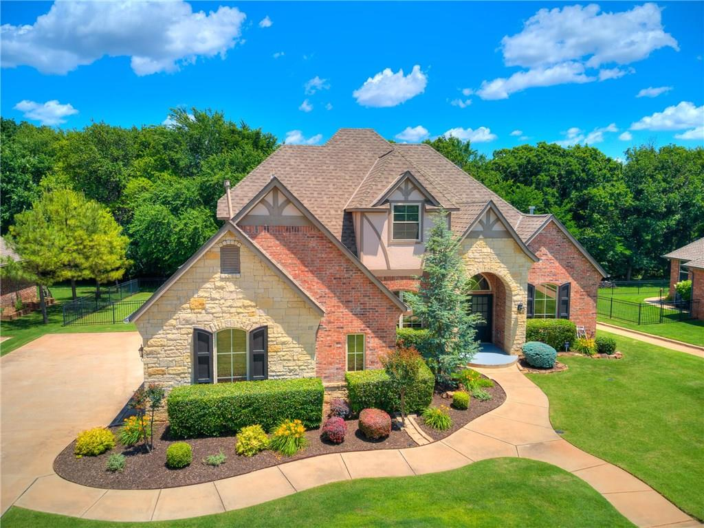 Looking for that perfect home where you feel you are out in the country watching the deer & wild turkey as you sit on your back patio having your morning coffee? This is your chance to live and experience all of those things & be minutes from all the amenities. Home backs up to a wooded greenbelt that gives you the best of everything & it's in Edmond Schools. Home is pristine & looks like it has never been lived in. Hand scraped wood floors are immaculate & beautiful. Handsome study w/built-ins.Huge windows allow for tons of nature light bringing the outdoors in. Stone fireplace makes the family room cozy, with an open kitchen that has double ovens, gas range, 2 sinks and an eat in kitchen. Master is huge with those wonderful wood floors, masterbath with 2 large walk-in closets. Upstairs boast 2 bedrooms with a jack & jill bath, 1 bedroom with a full bath & a large bonus room. Surround sound in family room & outside patio. Storm Shelter in garage. This home is pristine & move in ready!
