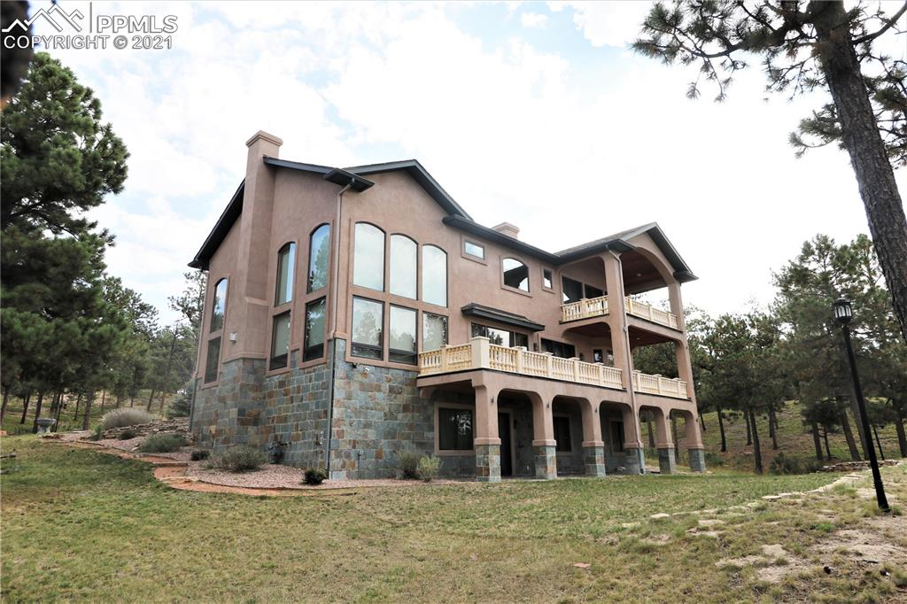 This is a stunning Custom Villa Home.  Located in Cathedral Pines on 4.6 treed acres. The grand entry way is inviting and boasts a hand carved stair case made of imported beech hardwood.  This beautiful stair case will take you to all 3 levels yet if you wish to take the easy way, all levels are accessible by a Cherry paneled elevator. The home has Egyptian marble throughout.  The great room has ceiling's that are2 stories high and has 2 walls of windows allowing views of the mountains, trees and so much natural sunlight.  The fireplace is absolutely gorgeous with a carved marble mantle. The gourmet kitchen has custom Ash cabinetry, a beautiful carved marble vet hood and a 2 granite sinks.  This kitchen is very spacious and has a large island with a sink, the counter has a built in deep fat fryer and last but not least a huge walk in pantry. High end appliances.  The kitchen opens to a balcony that is made from marble and slate, great for entertaining and relaxing with the great views of Pikes Peak.  Upstairs you have 4 bedrooms and 3 bathrooms.  The master retreat opens to a private balcony that again provides views of Pikes Peak. The master has plenty of room for a sitting area, a huge master bathroom with a very large jacuzzi tub and separate shower.  The walk in closet is wood lined and has lots of shelving, drawers and storage.  The basement has been designed for family and fun.  There is a large theatre room with fiber optic lighting and surround sound, along with raised seating.  You have a wet bar and a wine room.  The 3rd marble fireplace  makes this area great for entertaining and enjoyment.  The basement also is a walk out to a courtyard.  And this home has so much more, 9-10 ft and higher ceilings, 8 ft solid cherry doors Radiate heated floors, custom crown molding.  All located in Cathedral Pines with 810 acres, 450 of which are parks and open spaces. Miles of trails, multiple ponds, water features and picnic areas. This could all be yours.