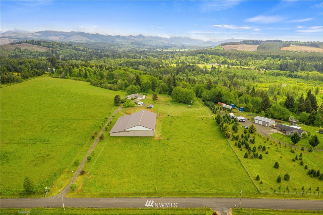 """Horse lovers take notice! BACK ON MARKET due to buyer financing. This private, picturesque, equestrian paradise w/ thoughtfully designed 4 bed/2 bath 2460 SF home on 9.77 acres includes fully enclosed 70x144 arena. Perimeter fenced, cross-fenced, partially field-fenced for goats, w/ fenced backyard. Main barn is 106x144 contains a well lighted arena w/ sand footing. Arena attachment has birthing stalls & 11x24 heated tack room w/ 6"""" insulated walls & wall-mounted saddle racks. 2nd barn is 48x36 with stalls, as well as a 10x11 garden shed & new 10x11 woodshed. Weaving through the trees along the driveway, you'll forget you're just minutes from town & a few miles from I-5. Choice equestrian bridle trails close by. Don't miss your 2nd chance!"""