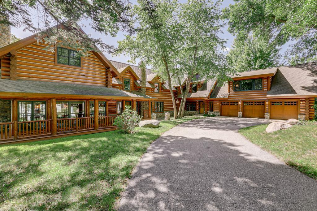 This home looks & feels like a resort getaway, a stunning log lake home located on .73-acre lot with abundance of parking for your guests! 182-ft of lake shore Green Lake!  Custom built by Rocky mountain Homes-undeniable craftsmanship including 12-inch milled logs with Swedish cope & WeatherLock Spline for tightness & energy efficiency. 2-story great room featuring a 26-ft ceiling, wood-burning fireplace + floor to ceiling windows providing breathtaking lake views! Solid hardwood floors throughout. 4-season porch with wood-burning fireplace & easy access to the wrap-around deck. UL guest quarters + loft area. Kitchen offers big island with plenty of seating, top of the line appliances & beautiful built-in buffet. A butler's pantry includes even more storage, built-in shelving & desk. UL 5 bedrooms including a private Master Suite. Above the garage is a private suite with living & dining area, kitchenette, vaulted bedroom & bathroom. Too many details to list - A total MUST SEE!