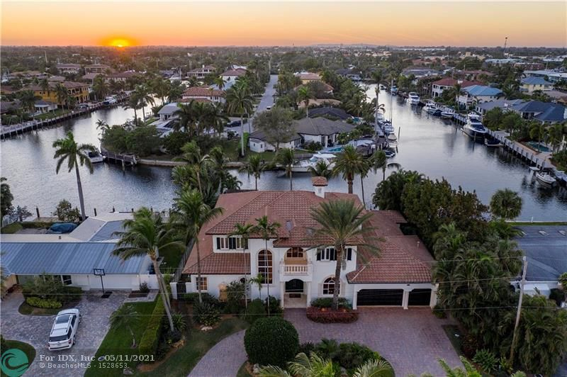 Set in one of the most desirable locations, this custom built traditional style deep water home easily becomes today's west indies or coastal style look. You enter through a dramatic grand foyer to look through to 100 feet of unrestricted waterfront on a 125 ' wide canal with turning basin. The impressive first floor master suite and waterside office, fantastic storage make this home so easy to enjoy. Laundries on both floors, two well positioned powder rooms and the four upstairs bedrooms and large den currently used for a theater give the new owner so many options. The gorgeous mahogany kitchen cabinetry and the  open family room with breakfast area,wet bar and lovely water views make for the perfect place to relax. Amazing outside  living areas complete this home which has it all.