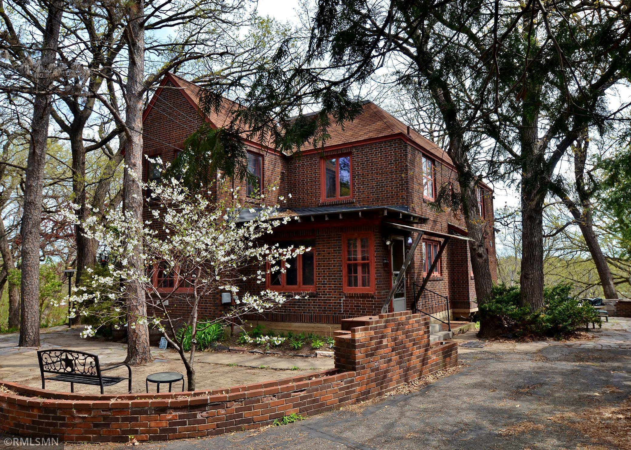 This amazing two story brown-brick English Tudor style home overlooks over 100' of Mississippi River frontage. It has had just one owner for last 60 years and needs a new owner to update it to modern standards. It has fantastic views of the Mississippi from several rooms and a huge two story living room with cathedral vaults and a Juliet balcony overlooking from the second floor. Wonderful stone courtyard and patio for outdoor entertaining. There is approx. 3/4 of an acre, level area by the river w/a granite fireplace, storage shed and covered picnic shelter. On the acre above between the house and street, there are fruit trees garden, blacksmiths forge and the remains of a lighted bocce court. It needs work but the location and style will make this a rewarding labor of love for someone. Sellers are including a $10,000 roofing allowance.