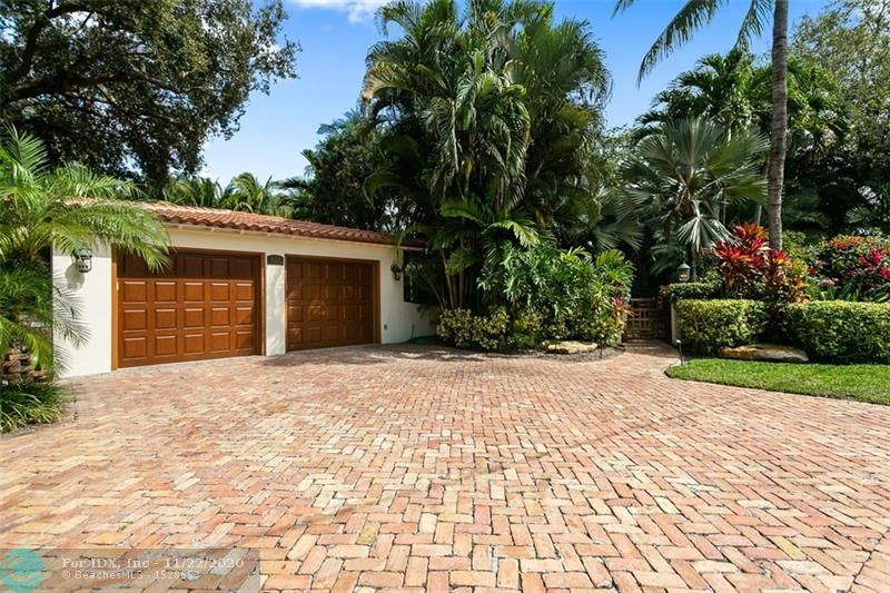 This secluded riverfront residence provides privacy and elegance within a tropical setting on the banks of New River in Fort Lauderdale. Mature foliage surrounding the pool creates the impression of a private island, all with the backdrop of boats along the waterway. The 15,000 sq ft property enjoys 103' of prime river frontage with a concrete dock spanning the entire length of the waterfront and features a boat lift. The large lot is set on one of the best streets in the city within the exclusive enclave of Rio Vista. Inside the home we find exposed beam ceilings in the main living area, Jerusalem stone countertops in the kitchen, cherry cabinets and granite in the bar and a built-in 250 gallon saltwater aquarium. The covered outdoor summer kitchen makes this space ideal for entertaining.
