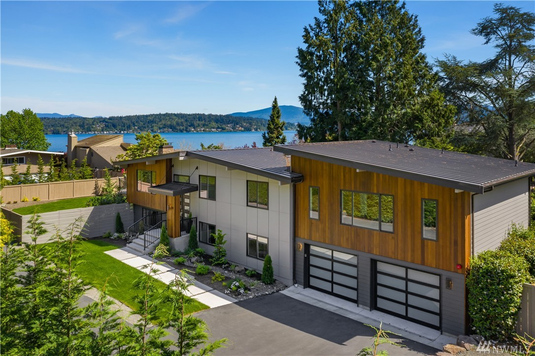 Better than new move-in ready residence with a NW contemporary/mid-century modern vibe. Lush landscaping & dreamy lake views abound. Crisp, clean lines and a wide open floor plan that lives large! Enjoy an amazing level of finish work & design detail throughout. Master suite on the main with 5 pc spa bath & huge walk in. The lake view deck is perfect for BBQ's. A flat, fenced lawn is ideal for croquet! 5 beds, 4 baths, office, work out rm, kitchen, wet bar, 2 laundries. Great Microsoft access!