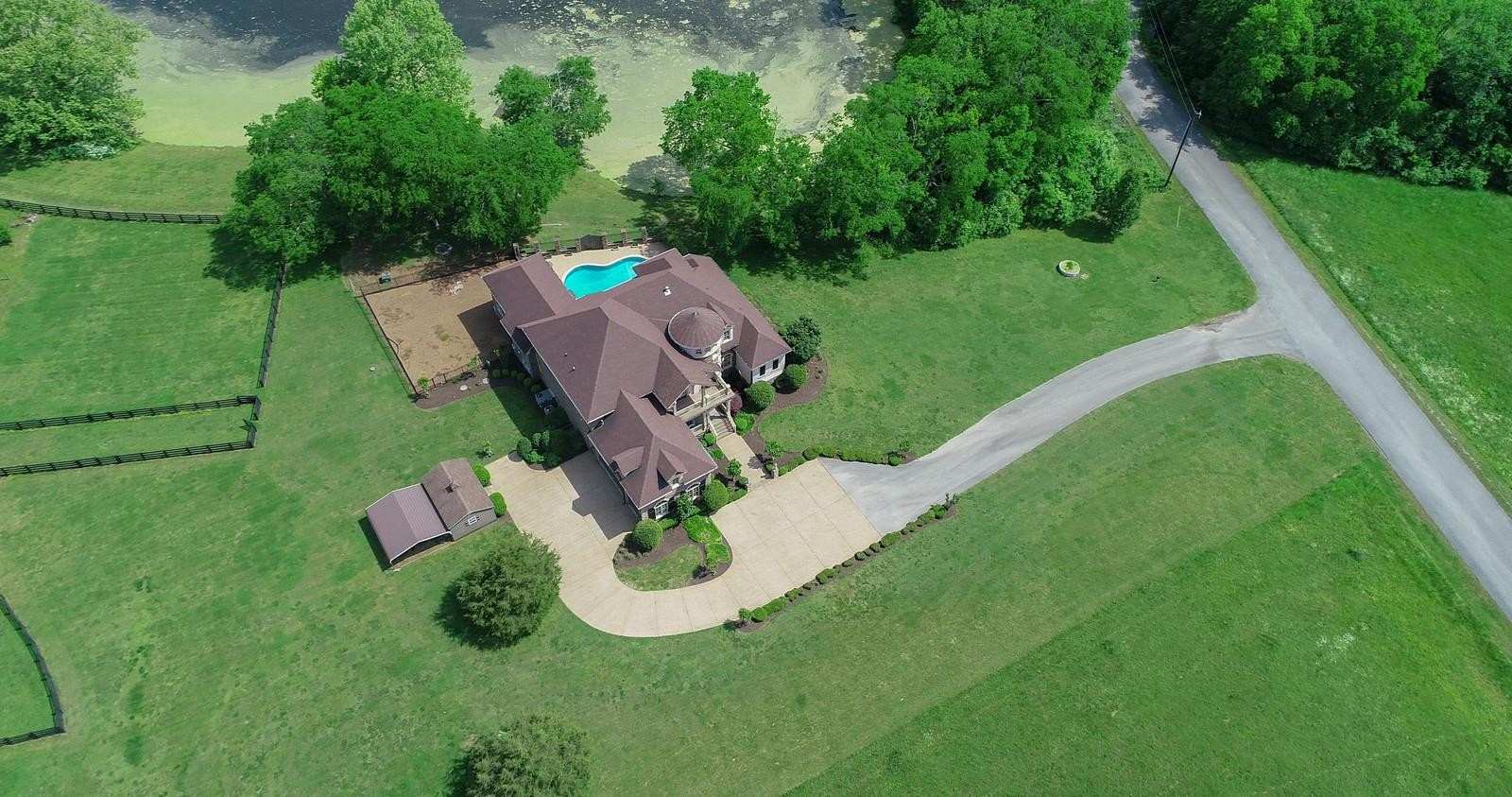 Magnificent estate home on 98 pristine acres. Panoramic views of the land & it's own private 3 acre pond. This one has everything. Gated entry, land is level & pristine. Surrounded by the Harpeth River which adds to the privacy. The home has everything you could ask. Gourmet kitch w/wolf appl. & butler pantry. Down Master w/huge walk in closet & dream master bath. Property has 2 additional homes that could be rentals or guest houses. Several Barns & plenty of room for horses.