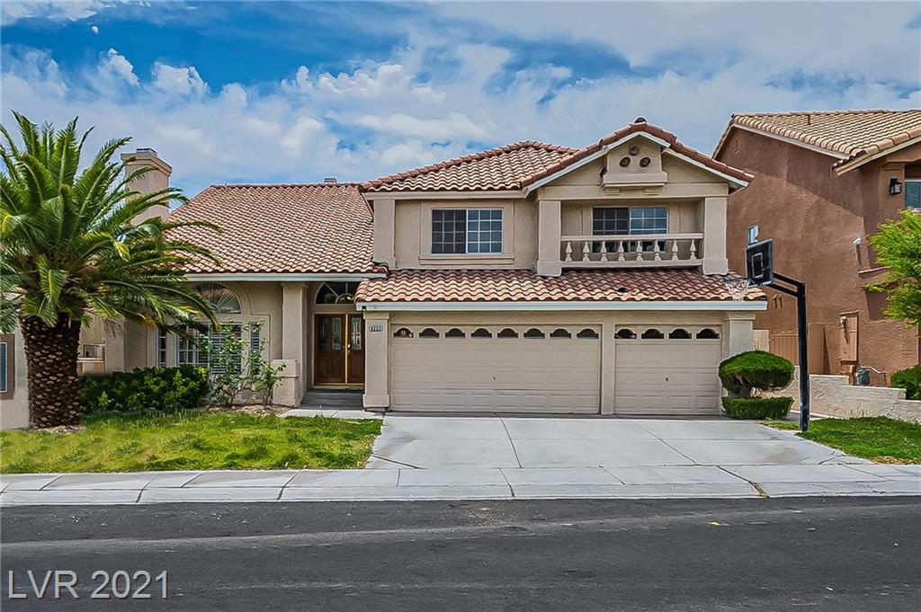 This Las Vegas two-story home offers an in-ground pool, a patio, granite countertops, and a three-car garage.