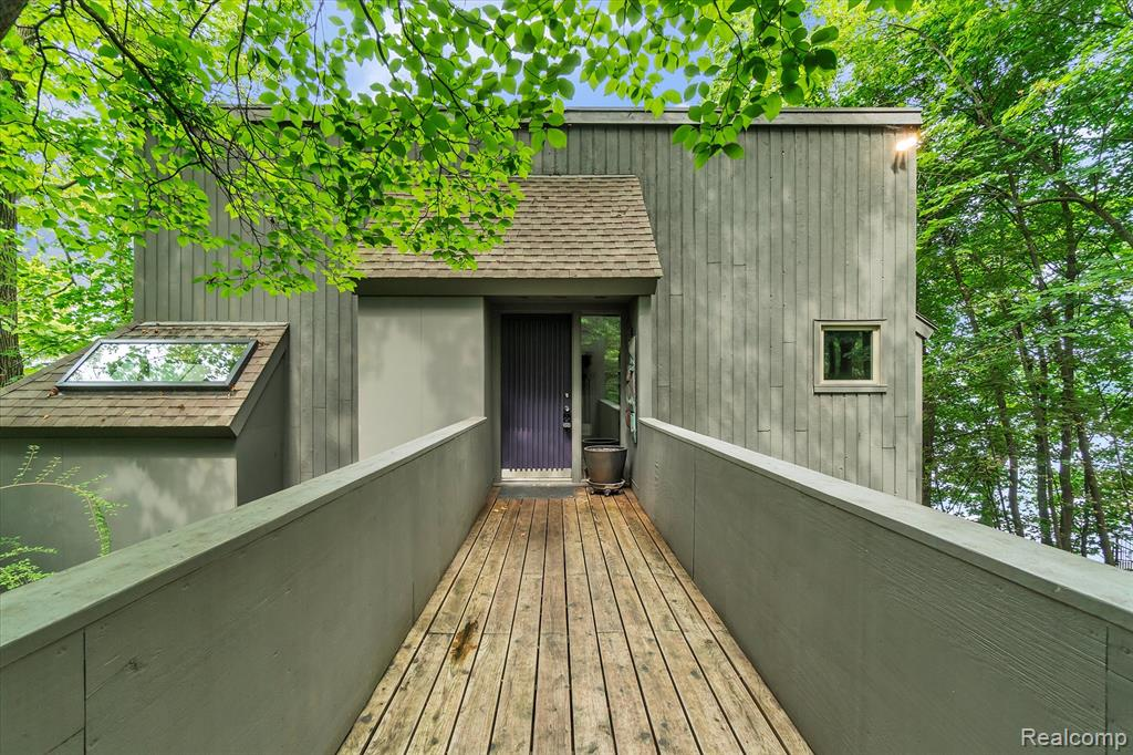 """Architects, arborists, artists flock to this custom-built lake home! Built by locally famed David Osler - an artistic architect who was inspired by the homes at Sea Ranch in Sonoma County, CA - custom-designed this home based on the naturalistic topography of its lot. This private """"natural lot"""" with 77' of Strawberry Lake frontage has been purposely left untouched to preserve the architect's original vision for a nature-surrounded, private, environmentally-blended property. Eccentric upscale interior has soaring ceilings, large bedroom sizes, and vintage era-specific finishes. Utilizing every interior nook as a cozy reading spot, bird-viewing setting, or gathering zone - this 2,000+ sqft home has unique surprises around every turn. Use the balcony and huge multi-level deck to enjoy the views and sounds of nature, including bald eagles, blue heron, loon, native birds. New picture windows. Watch the fall colors roll in from your lake home w access to the entire Portage Chain of Lakes!"""
