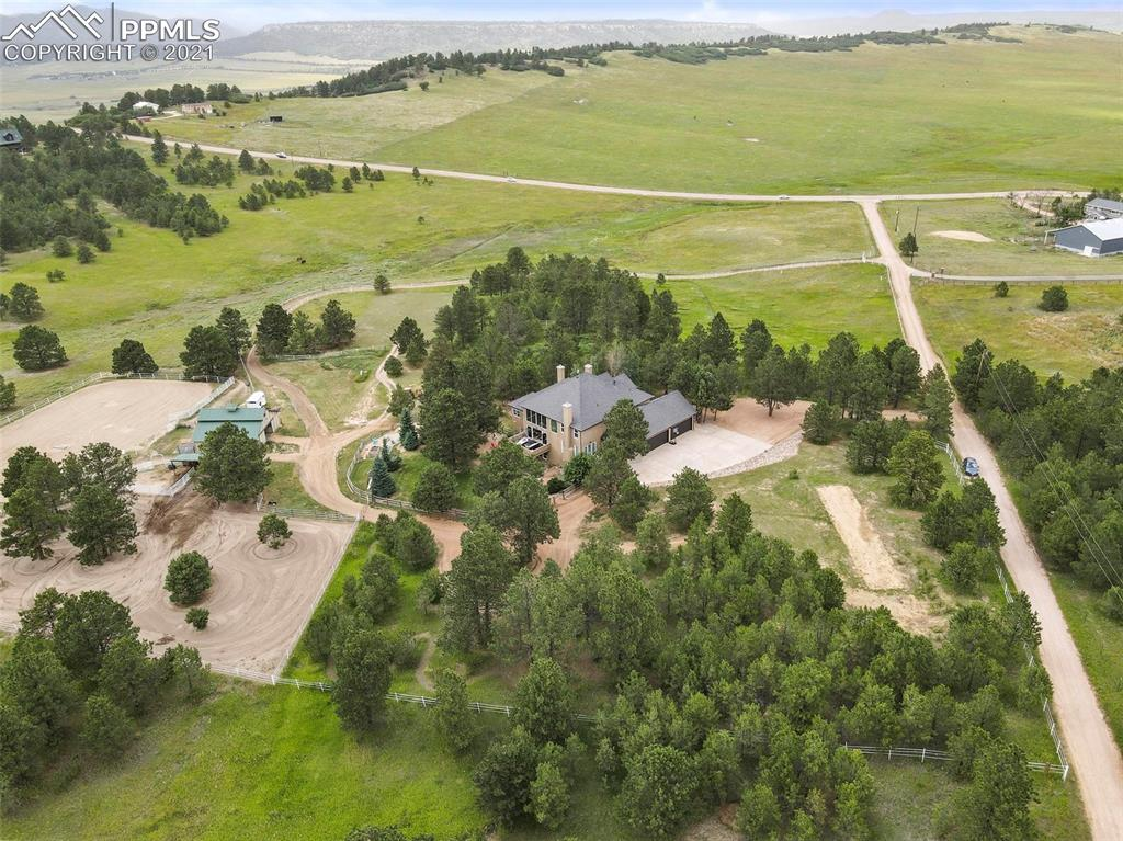 Stunning *sub-dividable* 21 acre custom equestrian paradise is the only modern estate of its kind with an unparalleled 2 minute drive to I25 in a tranquil park-like setting - views from every oversized window! True Colorado luxury living combined with real access to Denver and Colorado Springs simply cannot be found anywhere else. Live on 21 gorgeous acres only 30 minutes to Park Meadows Shopping Center in Denver and 15 minutes to the Air Force Academy with Palmer Lake and Monument town centers each less than five minutes away - El Paso County taxes right on the Douglas County line! This 7400 sqft custom gem is loaded with upgrades including real wood floors, abundant natural light w/ oversized windows & plantation shutters, 21 ft ceilings in foyer with grand staircase and enormous great room with huge fireplace & access to large deck, 10 ft ceilings in basement game room & theater with LVP, fireplace, wet bar & wine cellar w/ full guest bathroom and fifth and sixth bedrooms framed in with doors and walk in closets (not dry walled - currently a gym & meditation room) and 7th jack & Jill bathroom roughed in & framed between, 10 ft ceilings in Master Bedroom w/ private deck, sitting area with fireplace and huge 5 piece en-suite and walk in closet, 12 ft ceilings in the home office with fireplace, 9 ft ceilings in dream chef's kitchen with 10 ft hard rock maple island, 2 ovens, 5 burner gas range, custom leather finish granite, remodeled mud/laundry room, 3 beds w/ en suite upstairs overlooking 2 story great room, 2x6 construction, 5 gas fireplaces, 2 gas stubs (no propane tanks here), 4 decks/patios for outdoor entertaining, 36x36 4-stall barn w/ tack room, two loafing sheds and enclosed paddocks, 70 x 160 ft arena with all 21 acres fenced for horses & over 1 acre fenced for dogs, no covenants, RV parking w/H2O & power! A rare opportunity just 2 minutes to I25 w/ the new bridge at County Line - enjoy or subdivide into 5 acre lots for development in a prime location!