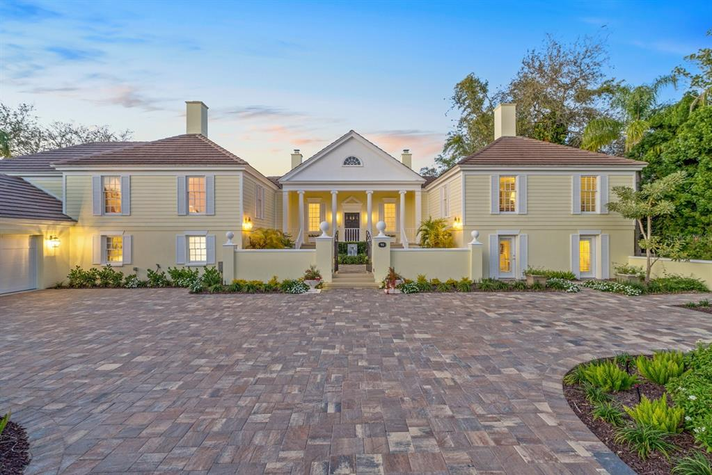 Iconic architecture in Sarasota's premiere golf and country club. This magnificent 4-bedroom estate was designed and built by Bo MacEwen and brims with the essence of warm, Southern hospitality. Bo was the original architect for The Oaks and he created this lakefront testament to form, symmetry, and serenity as his own residence. Renovated in 2017, every detail expresses an effortless sense of style & charm. Step inside the regal entry gallery with 12' ceilings and black and white marble floors. Host unforgettable evenings in the lavish living room with paneled gas fireplace, built-in bookshelves, and French doors leading to screened porch with long lake views. Let the spirit of culinary adventure take over in the new kitchen with custom cabinetry, Sub Zero refrigerator, Wolf range, quartz countertops & porcelain tile flooring. Master suite is designed as an inner sanctuary where lake views are in concert with elaborate details including moldings, bamboo floors, fireplace, and dressing room. Luxuriate in the master bathroom with large shower, marble tile & elegant vanity. Three additional en suite bedrooms are spaced throughout the home to maximize privacy for your guests. Exterior living spaces are perfectly in tune with gardens, lush landscaping & the private natural surroundings. New saltwater pool with travertine terracing overlooks the lake. The Club boasts two 18-hole championship golf courses, first class amenities, while Sarasota's cultural treasures and white sandy beaches are moments away. Oaks Club Membership is Required.
