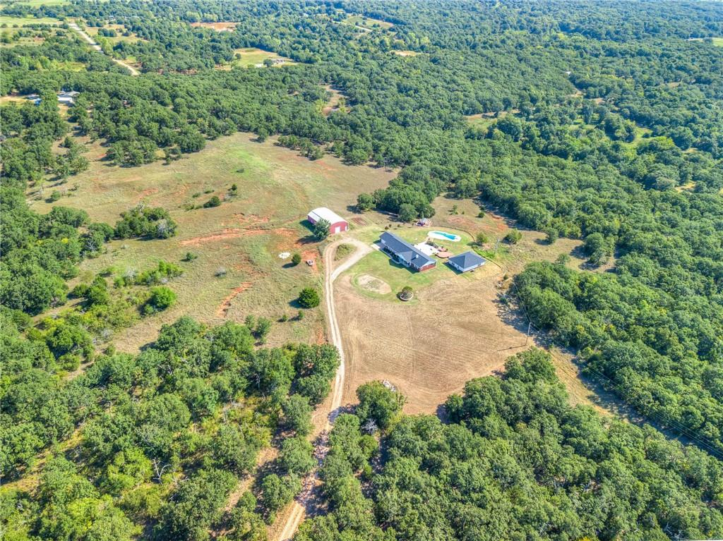 With an additional 62 acres available for a total of 112.17 acres, you could social distance so hard it wouldn't even have to be social any more.  Built on the top of a hill in a tree-lined clearing, this property offers seclusion without having to forego the nicer things -- an in-ground pool, huge concrete patio with a deck, 40x60 insulated workshop, 1200 sq. ft. guest house, and finally, seclusion doesn't mean 'disconnected' with OEC fiber already run to the pole!  This is a true 4 bedroom, 2 living areras + Study!  In the main house you have all stainless steel appliances, including double ovens.  The window over the kitchen sink looks out over the patio, pool, and deck and the kitchen itself is completely open to the 2nd living area.  Updated master bathroom with rain shower head, vessel sinks, and a deep jetted tub!  Guest house has a kitchenette, full bath, 2 living areas and a third that can be closed off as a bedroom!  Additional land consists of 6, 10-12 acre properties.