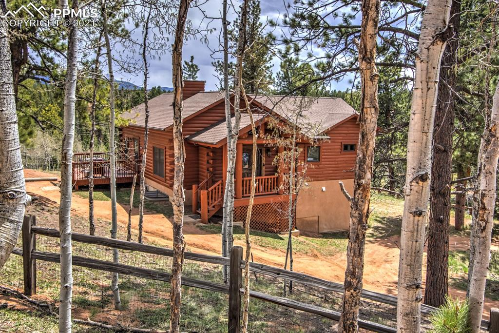 True Mountain log home with Pikes Peak views, located in desirable private fishing community, Spring Valley! Only 20 minutes West of Woodland Park, on County maintained roads. Home has been used a second home and vacation rental for many years, and can be purchased as a turn key, furnished home. Spectacular features of the home to include, entry mud room for coats and boots in winter months, great room w/ beamed ceilings and vaulted architecture, stunning double sided, stacked rock, gas fireplace