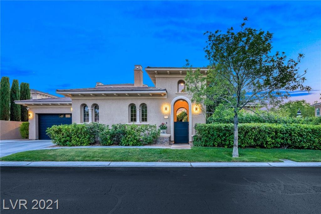 """This multi-level home in Summerlin Village offers distinctive spaces and a blend of artistry and rusticity. With more than 4,900 square feet, the home is a unique interpretation of a traditional """"castle"""" with a circular tower. The open floor plan includes a colonnaded great room with rugged ceiling beams, a massive stone fireplace and three sets of French doors leading to an arched patio. A spacious family den adjoining the kitchen has built-in bookcases, impressive fireplace, and features a wall of glass that overlooks a charming lagoon pool. The kitchen's blend of golden-tone tile and solid surface counters with charcoal-painted cabinetry is uniquely appealing and designed for entertaining. The master bath is a dream space, with dual vanities, a huge walk-in closet/dressing room, oval soaking tub and separate shower. This well-planned home has four bedrooms, five baths and garage parking for three vehicles."""