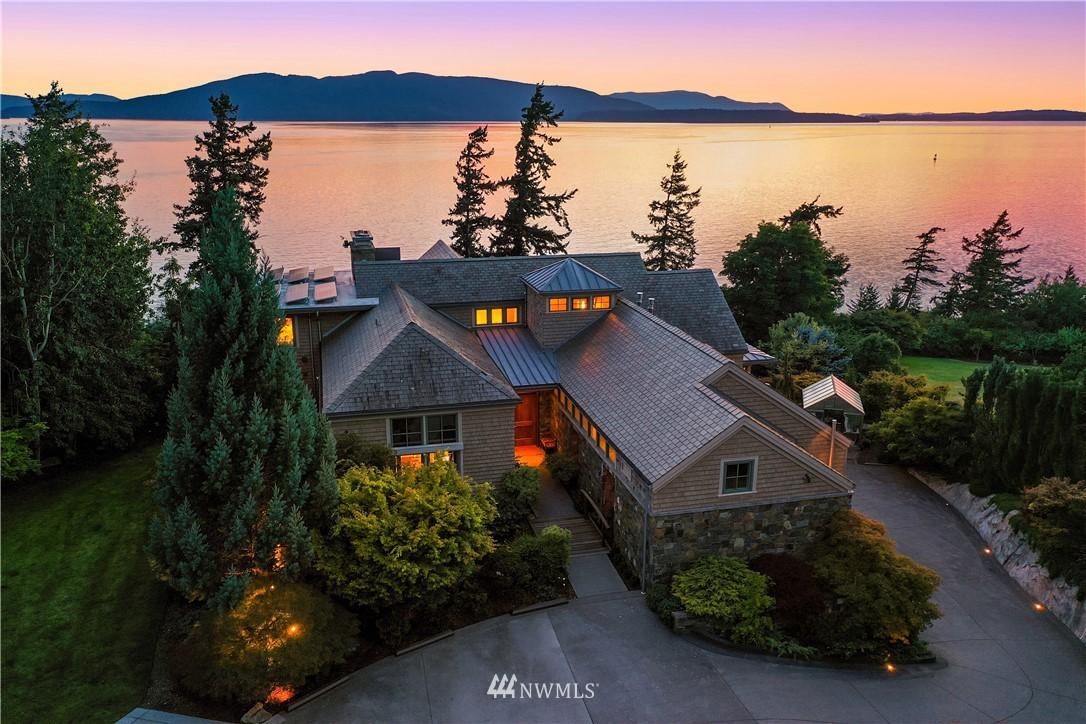 """Rare opportunity to acquire a significant 2.36 acre estate with sweeping views of Bellingham Bay and the snow capped mountains beyond. The sophisticated Northwest Contemporary home was custom built with exacting attention to detail by Pearson Construction in 2008. A substantial, light filled great room, bookended by distinctive fireplaces opens onto to an expansive Ironwood terrace extending across the back of the home. A handsome library is a jewel box to showcase your books and treasures. Downstairs, it's all about entertainment: billiards and game rooms, a professional style theatre and an indoor """"Endless"""" pool and sauna. Northwest specimen plants frame the landscape where a rolling lawn leads to concrete stairs down to the beach."""