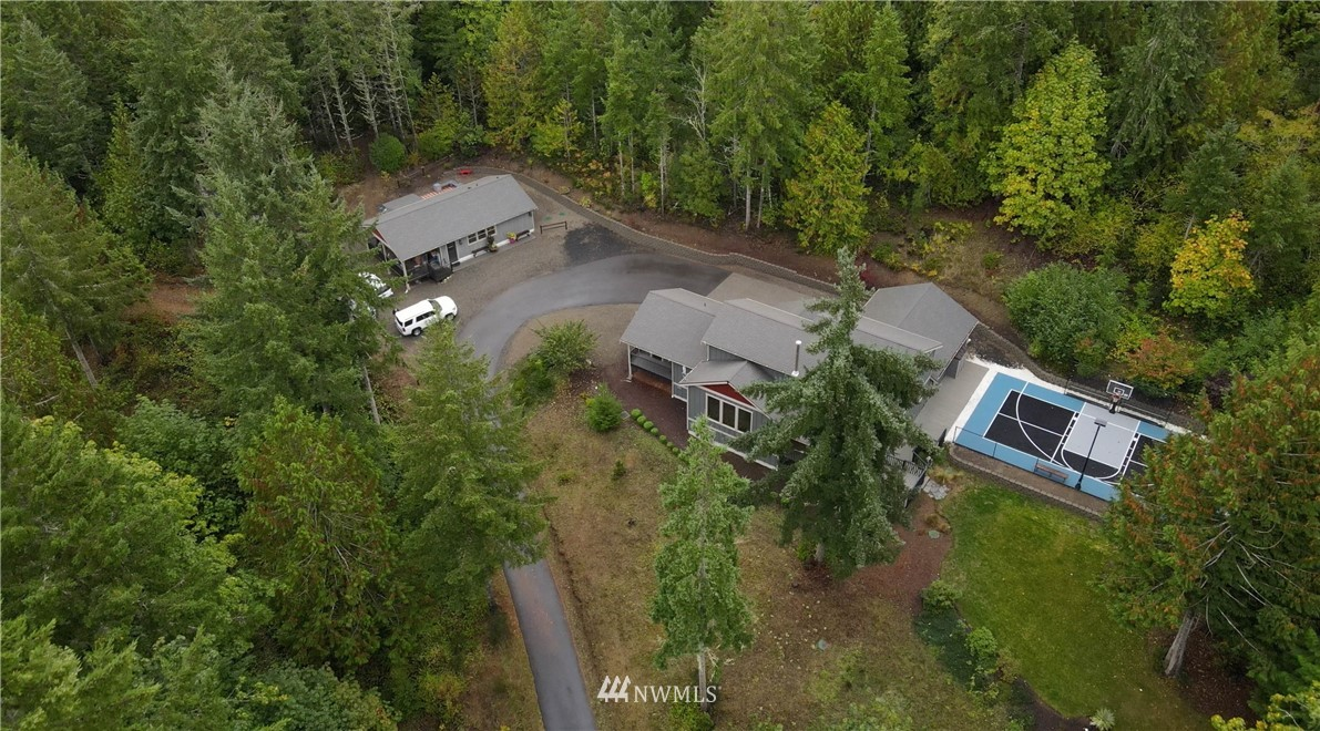 A peaceful escape awaits in this custom built 3BR/3BA + office home on three acres w/ peek-a-boo views of the Olympic Mountains. This one-of-a-kind property built in 2013 features a gated entrance, fully permitted 768 SF ADU, 200 SF detached shop, sport court, play area & outdoor fire-pit.  At the heart of the home you'll find an oversized kitchen w/ high-end cabinetry & large island perfect for gathering. Cozy up in the main floor master suite w/ jetted tub & private deck. Upper level includes two more bedrooms & a full bath. Every bedroom has its own walk-in closet & the home features three split systems for heating & A/C! Both interior & exterior have been freshly painted and both dwellings are wired for generator. Just minutes to GH!