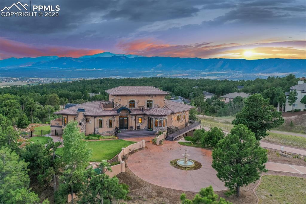 Custom Palmer Ridge Hilltop Tuscan Villa with SPECTACULAR mountain / Pikes Peak / 360 degree views  * Quality build inside and out * The entire home is heated with digitally controlled active and passive solar hot water radiant heat in all the floors including the garage * Arched Alder Entry * Travertine Floors * 3 Fireplaces * Stucco and stone * Granite and stainless steel * Stately Stamped Concrete Driveway * Extravagant Fountain and stamped concrete circle courtyard * Upstairs FLEX bedroom suite / library / office with gorgeous views off private balcony * Full Wall of South Facing Windows & Full Length Deck Looks Over the Front Range Mountains & a Sea of Tall Pines. This Home is a Fortress of Energy Efficiency! Solar panels and Tesla-ready with 220 in garage * Brand new carpet on main and upper levels * All new appliances * Triple Pane Pellas * Cement Tile Roof plus metal accents * Ten Foot Ceilings Throughout the Basement * Custom Fiberglass Window Wells Carry the Tuscan Brick Theme * Theater + Theater Lobby with Custom Wet Bar * Walk-In Wine Cellar and Two Large Storage Closets with Shelves * Two Separate Entrances to Basement * A Full Bath and a Very Unique Custom Travertine Tile Curved Shower in the Second Bath * Nine Zone Sprinkler System includes Drip Irrigation and future zones for the Far Side of the Driveway * 4 Car Drive Under Garage boasts 1,100 Square Feet of Heated Space, Custom Wood Insulated (R20) Garage Doors * Solar, Passive and Active, highly efficient tube system heats the home through radiant hot water floor system and domestic hot water * High Efficiency Munchkin Heating System for Back-up to solar * Foamed 2x6 walls * Convenient location just 20 minutes from downtown Colorado Springs and 40 minutes from the DTC