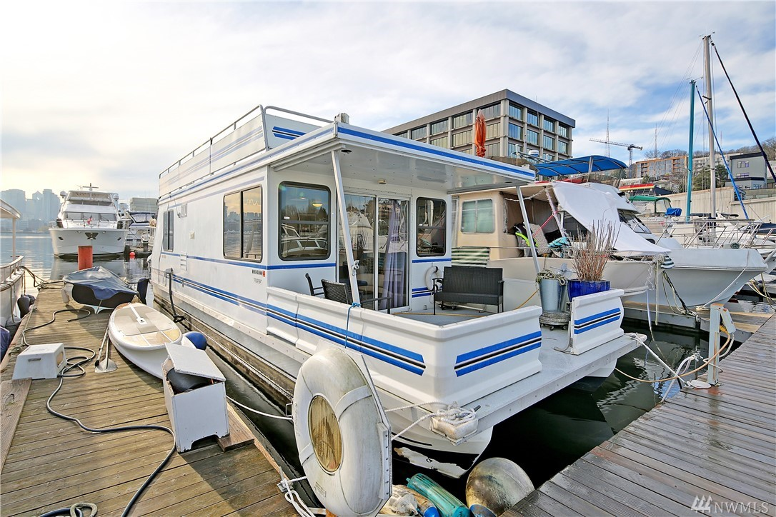 """""""Major Price Drop just in time for summer fun"""". The city at your fingertips and the lake at your toes. This houseboat is the idyllic Seattle experience.  Sip your coffee on the covered front porch or relax on the couch while the lake gently rocks you. Full roof top deck offers sweeping postcard views of Downtown and Gasworks Park and waterslide. Modern and bright open-concept living close to SLU, Fremont, and Downtown. Leased liveaboard slip in pet-friendly marina, $1,195 PM."""