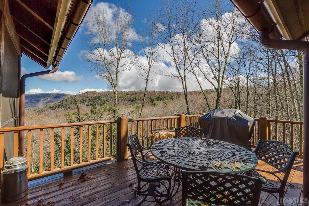 Located in the exclusive and gated community of Cedar Hill, this gorgeous home on almost 3 wooded acres is offered furnished (with a few exceptions) and has exceptional views of the majestic rock face of Cow Rock, Laurel Knob and Lonesome Valley from every room.  This meticulous retreat was extensively renovated in 2020, and features a vaulted, beamed living room centered around a stone wood burning fireplace - where the surrounding vistas are highlighted through a wall of windows. Random width heart pine floors are featured throughout the main living spaces. The inviting covered screened-porch, just off the living room is the perfect place for enjoying coffee on a cool summer morning or gathering with friends to have dinner and drinks. The gourmet kitchen and dining room are open with vaulted and beamed ceilings and are perfect for entertaining. Kitchen appliances, including a Wolf range/stove are all new. The updated master suite and one guest suite are both on the main level. In the walkout lower level are two more guest suites with updated baths and a family room along with a  wrap-around covered deck.  The split floor plan provides privacy for guests and owners. The 2 car garage is attached by a breezeway.   The crawl space is encapsulated, all new interior paint. Cedar Hill is very private yet ideally located just a few minutes from the supermarket, restaurants, retail stores, hiking and country clubs.  The home is serviced by 2 hot water heaters, one is electric (approx 60 Gallons) and one is gas (approx 132 Gallons) which services the master bath and left side of the home. 2x6 exterior walls for extra warmth. Whole house dehumidifier.