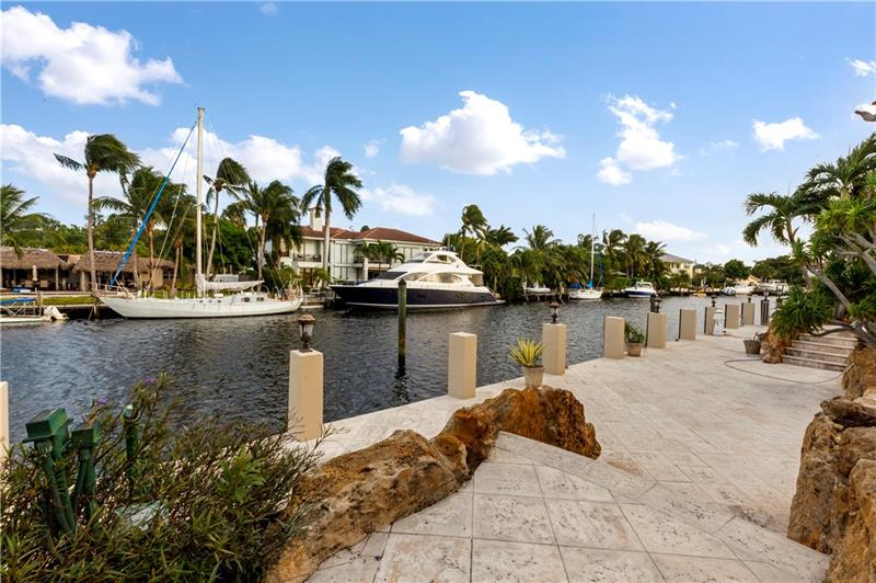 Waterfront living at it finest with 120 ft. of deep waterfront, a concrete dock & only mins. to the inlet & Atlantic Ocean. This property is one from the inner point with breathtaking waterway views. The S. Florida lifestyle doesn't get better than this tropical backyard boasting a full summer kitchen, waterside pool, large patio area & lush landscaping. Soaring ceilings, an open floor plan & luminous rooms looking onto the waterway. The heart of the home is the gourmet kitchen which over looks the breakfast area, wet bar & family room. This residence boasts a soaring grand entry, 2 story formal living room, formal dining room, elevator & for those who work from home a custom home office. The luxurious master suite & bathrooms are enhanced by a waterside covered balcony. Sq ft from IMAPP