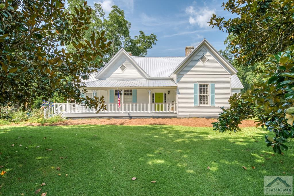 This beautifully renovated historic 1900's bungalow in Athens, sitting on 3.72 acres, is a little bit of country in the city.  Shops and restaurants are located just minutes away! So many renovations to name, here's just a few:  new metal roof, new paint throughout the interior, restored original hardwood floors, new ceiling fans, updated electrical, new water heater, new kitchen appliances, new metal roof on the barn, new fencing and extensive landscaping that includes a flagstone entryway.  Make this home your own by using the rooms as you wish: bedrooms, flex rooms, study/office space or dressing rooms.  Enjoy evenings spent on the covered back porch & the peace and tranquility in your backyard & the green space out back. You have enough room to put in a garden and there are fruit and nut trees located throughout the property.  Bring the chickens, goats and horses and start your own farm.  There's also a walking trail that was created throughout the woods. The sky's the limit in this beautiful home! The property is on 2 city lots and can be subdivided.
