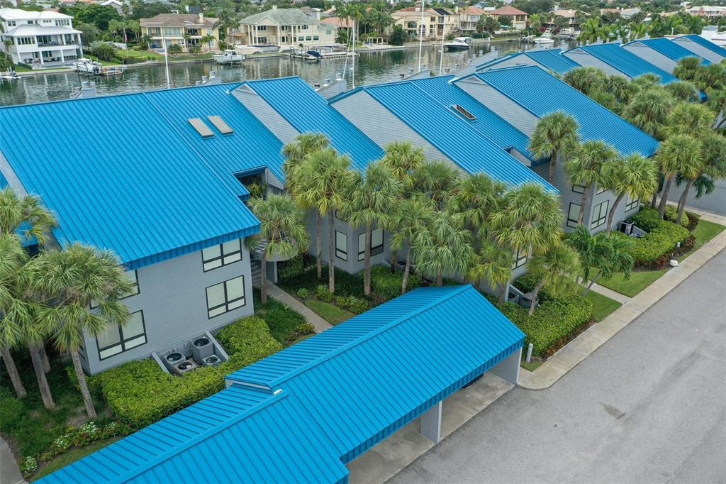 Enjoy waterfront key living in this sought-after boating community! Port Tierra is a fantastic community located near the end of the canal with easy access to the Gulf with no bridges. The owner put in roughly $80k in improvements in 2020-21 in this stunning, rare ground floor one story unit that has a completely open floor plan with great water views and sunsets.  Past the main entry opens up the extremely well-lit great room perfect for entertaining.  The living area has a wood burning fireplace and dual sliding glass doors leading out to a spacious covered deck.   The kitchen has white shaker cabinetry, white chevon style backsplash, quartz counters, farm sink, stainless appliances, cabinet pantry, and large breakfast bar that seats four comfortably and opens up to the great room.  A breakfast nook sits off the kitchen which could double as office space or a sitting area.  The spacious master suite has two closets, long dual vanity with drawer bank, quartz countertops, shaker cabinetry and a large shower area.  The guest room holds a queen bed comfortably and the guest bathroom has a shower/tub combo. From the outdoor deck, you are steps away from the swimming pool and dock compete with your own boat slip where the owner installed an 11k lift to the deep water canal.  This unit has a dedicated covered parking spot with overhead storage. Other features include: new wood grain tile throughout; crown molding; high ceilings; new recessed lighting; new lighting & plumbing fixtures; abundant guest parking.  Enjoy outdoor living, boating, fishing, restaurants and everything Tierra Verde has to offer. Minutes from Ft Desoto Park, St. Pete Beach, I-275, and downtown St. Pete & Tampa International Airport. Port Tierra is an extremely well maintained community with a strong association with newer 40-50 year metal roof, siding, exterior painting and pool redone. Condo association will be beginning restoring the community docs shortly and the assessment has been paid in full 