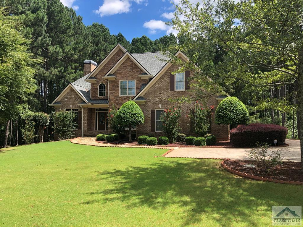 Located in highly sought-after North Oconee School district is Meridian, one of Oconee's flagship swim/tennis communities. This 4-bedroom/ 4.5 bath with master suite on the main offers site finished hardwood floors throughout main level and upstairs, a 2-story foyer with  inlayed hardwood, double French doors leading to an office, and large dining room with interior columns and a drop tray ceiling. The vaulted great room offers open living space with the kitchen overlooking great room with serving bar. The kitchen includes an island, granite countertops, tile backsplash, breakfast bar, and breakfast area. There are lots of windows across the back of the house that overlook the flat back yard. The Master Suite on the main is tucked away with lots of privacy featuring a large tray ceiling and lots of windows overlooking the back yard. The master bath includes large walk-in shower with frameless glass shower door, jetted tub, granite countertops with a raised vanity, raised ceiling, plus 2 walk-in closets. There is a door from the master that leads to a deck area with lots of potential, such as a private deck sitting area or even adding a screen porch. Upstairs includes 3 additional bedrooms, all with hardwood floors. The first 2 baths connect to a jack and jill bath, and the larger third bedroom includes private bath. The walk-out rear daylight terrace level is mostly finished with theatre area, wet bar overlooking pub table area, full bath, and a rec room, perfect for ping pong or pool table. Extras include stone walkway and accents, custom trim package, custom cabinetry throughout, large deck, 2 pantries, walk-in laundry with built in cabinets and laundry sink, pre-wired for speakers throughout and an intercom system, insulated oversized garage door, and wainscotting in garage. This is a fantastic location, only minutes to the schools, shopping, pager range to the hospitals, and easy access to the University of Georgia.