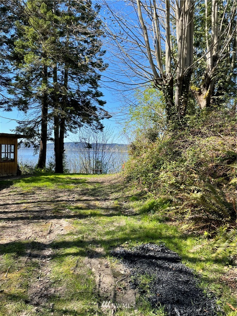 Exciting opportunity to own 99+ feet of high bank waterfront on over 1/2 acre in the beautiful Smugglers Gulch!! With views of the Olympic Mountains, Whidbey Island, and Puget Sound this lot will not disappoint. Enjoy the most beautiful drive into this private oasis, surrounded by trees & lush greenery. Build your dream home or summer cabin here! Lot has an existing driveway and level building site. The property will take development & site work along with your vision! Very secluded yet, minutes to town. Power + sewer on property, water in street. Property is marked. Community beach waterfront and large common area. Don't wait!!