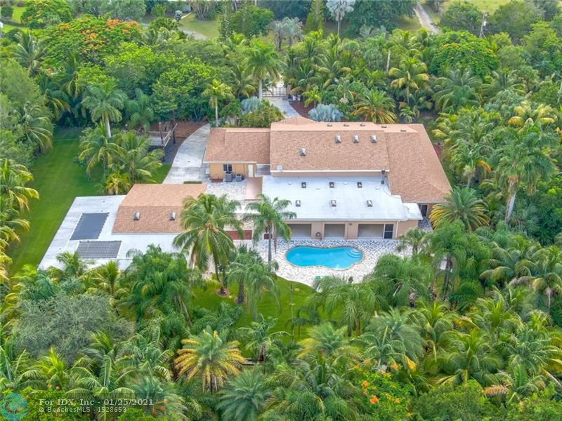 "BEST value in BBB Ranches! 2.5 acres of tropical paradise in the heart of Parkland. The custom built main house offers a private gate, 5 spacious bedrooms, 5 full baths, a game room, and a large family room with 5800 sqft. You will love the 15ft volume ceilings and open floor plan that can accommodate any lifestyle. Huge gourmet kitchen offering 42"" wood cabinets with soft close doors, and granite countertops. Freshly painted interior, 2017 roof, 2017 AC units, PGT windguard sliders, solar heated salt water pool, and a huge driveway for all your cars. This property also offers an enormous detached flex space with about 3000 sqft that can be utilized as a garage, stables, gym, or work area. This is a MUST SEE for all that are looking for a huge living area with private tropical landscape"