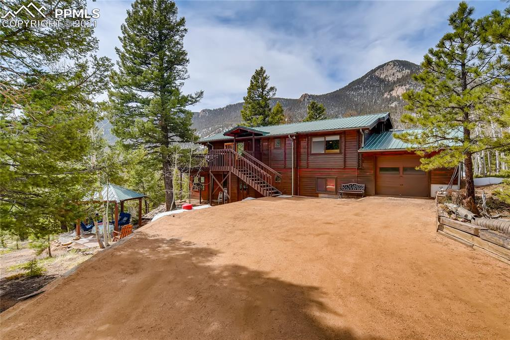 On top of the world! Beautiful cedar log home, nestled among the trees with unbelievable views of the mountains and Pikes Peak in the Crystal Park community. This home is tongue and groove built, which gives it a unique character and makes it well insulated. Walk into a spacious living room with walls of windows. The dining room and kitchen walk out onto a wrap-around deck. The Master bedroom on the main level has windows galore with views and 2 walk-in closets. The downstairs features a large family room that is attached to a sunroom. Also a wood stove to cozy up to on those chilly nights. 3rd bedroom is on the lower level with a full bathroom. Another unique feature in the lower level is a room that has a workbench for all your workshop needs. HOA fees cover Park Manager, Park Admin, maintenance crew (plow and maintain roads), gate security staff, mailroom, trash/recycling services, a stocked trout pond, and clubhouse with pool. Buyer to verify square footage. This is the perfect mountain retreat for family and friends, a great back to nature residence for year-round living, and if you want peace and quiet while working from home- look no further! Schedule a tour today to see this remarkable everyday getaway!