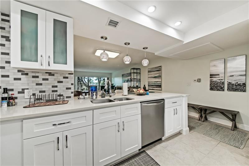 An artisan lived & loved here!! Check out the 3D tour of this exquisite updated unit that includes so many cool modern touches. So much craftmanship was put into the custom built TV wall and Bar that convey with sale.  TV in bedroom #2 also conveys.  All other contemporary furniture for sale. Unit was recently painted & HVAC disinfected. Panoramic golf views w/tropical oasis on screened balcony.  Open kitchen w/ SS appliances; there's tile everywhere w/ new carpet in main bedroom.  Impact windows bedrm #2, accordion hurricane shutters on patio, & hurricane panels for catwalk windows.  GE Electric panel; LED recessed lighting in kitchen & bathrooms. Association is truck & motorcycle friendly; $434.83 monthly fee includes INTERNET, Cable, & Water.  3 pool areas with grills & saunas.