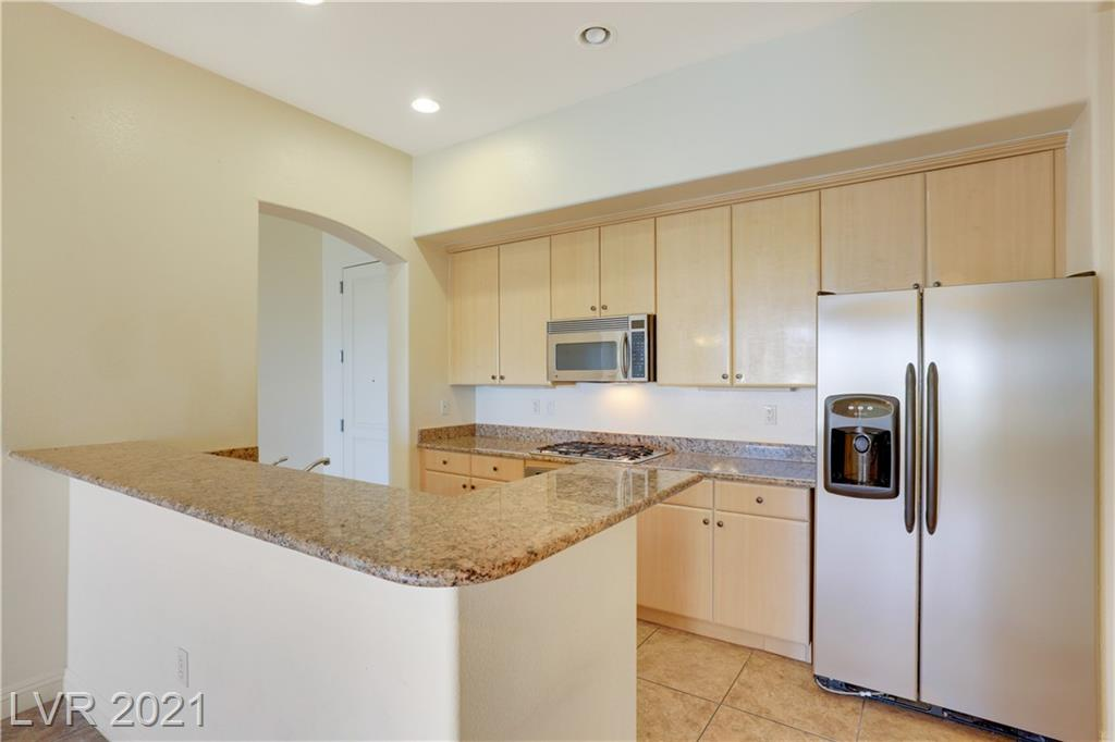 Resort-style living in fantastic 2BRD & 2BTH condo w/den on 2nd floor located in the Manhattan Condo community! This guard-gated community is located close to the strip. Amazing city and mountain views! Comfortable layout with family room, dining room & kitchen combined. Upgraded tile in entry, wet areas, dining area & all other areas have carpet. Efficient kitchen off entry is elevated w/lovely light cabinets, granite countertops, ss appliances, breakfast bar, built-in oven, microwave, recessed lighting & 2 pantries. Stunning arched opening w/square columns upon entry to the large den. Primary bedroom enhanced w/ceiling fan & walk-in closet & ensuite w/dual sinks, sit-down vanity, water closet & walk-in shower. Separate laundry room includes washer & dryer. Enjoy the large and relaxing balcony plus community amenities including clubhouse, swimming pool, exercise equipment, underground parking, play equipment & BBQ area.
