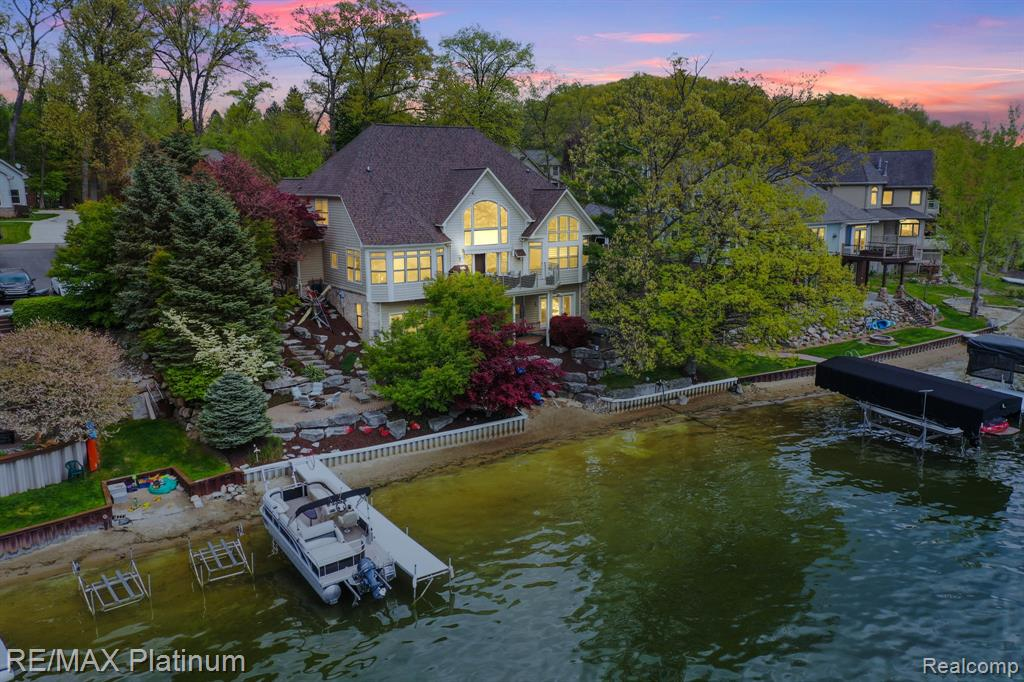 Remarkable Thompson Lake Estates Waterfront Colonial Boasting Contemporary Flare Throughout. Soaring ceilings from the foyer flow into the Great Room featuring sweeping views of the lake. Opening to the renovated kitchen, the floorplan is ideal for families. Brand new cabinets, granite countertops, & SS appliances will entice the family chef, while enjoying lake views & the sound of the waterfall while preparing meals. First floor master suite boasts vaulted ceilings, walk-in closet, & attached bathroom with new granite countertops & separate tub/shower. One princess suite & jack-n-jill bedroom arrangement in the upstairs plus a loft area. Fully finished walkout lower level creates the ideal lakefront entertaining space, with kitchen, rec room with second fireplace, full bathroom including sauna, & full gym. Walkout to the patio, with pavers leading to the hot tub overlooking the lake, & the full sandy beach. Fresh epoxy floors in attached 3-car garage! Get in with time for summer!