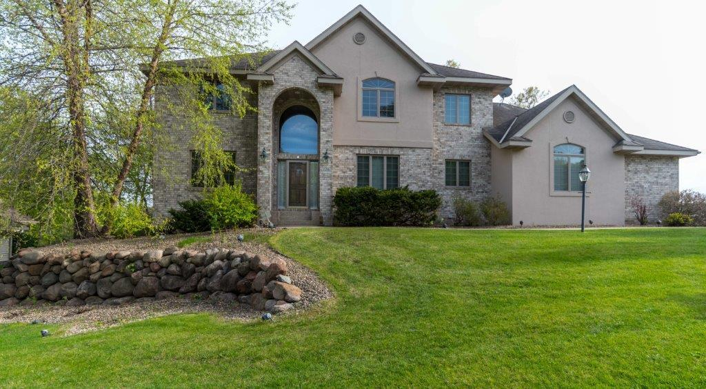 Value plus. 4900 total sq ft-3252 is already finished. $700,000 home across the street.  No detail went unnoticed in this stunning 2 story took into consideration the added upgrades during construction of this Tiffany neighborhood home. It is apparent with the attention to detail in the curved archways, intricate ceiling patterns, window shape varieties and appointed pillar sculptures. Solid wood flooring, granite/marble accents, paneled doors and wood cabinetry with lit glass fronts impress every discriminate buyer. It illuminates with sunshine and natural light that streams in through the abundant oversized Andersen windows all of which have grids adding distinguished curb appeal. High ceilings, large rooms and the open view catwalk give space a dimension of its own. 5 BRs, 3 full baths, finished laundry and 3 car garage have all been meticulously maintained. The full unfinished basement allows you to add your own personal touches.The deck is private, the landscaping is complete.