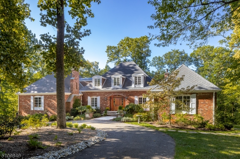Located on a quiet cul-de-sac, this striking updated 5-bedroom custom residence is set on 3+ private acres of grassy lawn, professional landscaping, and tall trees. Beautiful architectural details and finishes are found throughout the home including hardwood floors, built-ins, and crown moldings. The gourmet kitchen and living room open to an expansive IPE deck with a built-in grilling station overlooking the rear yard. The large family room has extensive millwork and masonry gas fireplace. The bright newly finished walkout lower level has undeniable appeal with an entertainment room with wet bar, bedroom with full bath, wine room, gym, and half bath. The magnificent exterior also includes a beautiful patio, irrigation system, circular drive with gated entry, 3-car garage, automatic generator, and new 5-bedroom septic. Close proximity to shops and restaurants, NJ Transit train, and major highways make this the perfect location. All of this and a highly rated school system.