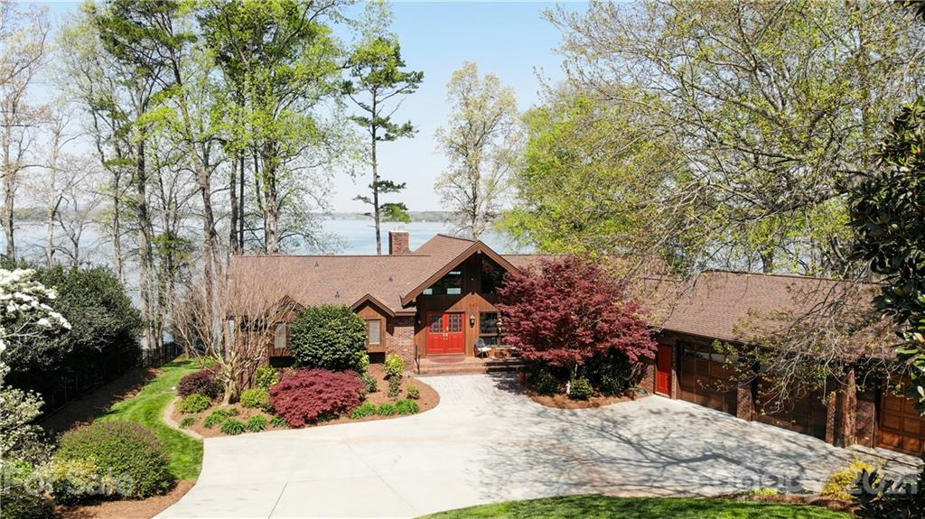 One of the Best 180 degree Waterfront Views on Lake Norman! Beautifully landscaped, hard to find Expansive Ranch home w/ finished walkout basement. Hardwoods throughout most of the main floor & tile floors on the lower level. Master Suite & 2nd bedroom/office/flex space located on the main level. All Bathrooms have been updated! The luxury Master Bath has a free standing tub & a true steam shower. Vaulted Great Room ceiling w/ wood beams, stone fireplace, & grand views of the Lake. Spacious kitchen w/ walk-in pantry & extra stove just behind in the mud room handy for those entertaining events. Relax in the enclosed sunroom w/ sliding doors all around or on the covered deck w/ retractable windows to the outdoors. Lower level boasts 3 spacious bedrooms, a bonus room w/ kitchenette, storage, updated full bathroom w/ 2 showers & a expansive patio w/ hot tub. Big covered dock w/ 2 slips. NO HOA! Sunset Views! Oversized 3 car garage w/ drain & hot/cold water spickets.