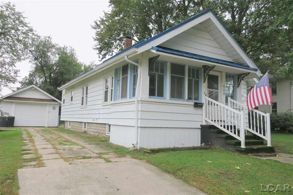 Nice Blissfield home on large lot close to schools and water fun park. Newer oak kitchen cabinets, includes, dishwasher, disposal, stove and refrigerator, large living room with sun porch for the cool summer days to sit. Newly remodeled bathroom with jetted tub and pedestal sink.  large upstairs all set up for 3rd bedroom with electric in, set up for a bathroom, needs plaster finish and carpet.  Beautiful natural original woodwork, enclosed back porch, tankless water heater, newer chain link fenced back yard, apple tree. The one car garage has a basement for extra storage. New over head garage door as well as side entry door and opener.   Newer metal roof on the house. All room sizes, square footage, and lot sizes are approximate. This information has been secured from sources we believe to be reliable, but we make no representations or warranties, expressed or implied, as to the accuracy of the information. Buyer or buyers agent must verify the information.