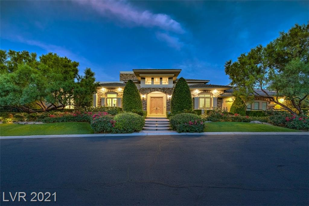 Traditional architecture blends with slight Tuscan influence, a true masterpiece, surrounded by lush green landscaping in the Promontory Ridge neighborhood in The Ridges. As you pass through double solid wood doors you enter a grand living & dining room with 18-foot ceilings & colossal glass sliding doors that bring you to a covered sanctuary under an extended cantilevered patio; offering complete views of the Las Vegas Valley and Strip & occasional lightning storms crossing the valley. Single-story home with the primary bedroom, & two additional bedrooms on the main level. When ready to immerse yourself in a world-class cinema, ride the commercial-grade elevator to the lower level THX sound engineered theatre. Afterward, take the elevator up to the spacious rooftop deck equipped with a wet bar & endless strip and valley views. Confirm your appointment now to view this meticulously designed home before the opportunity escapes you.