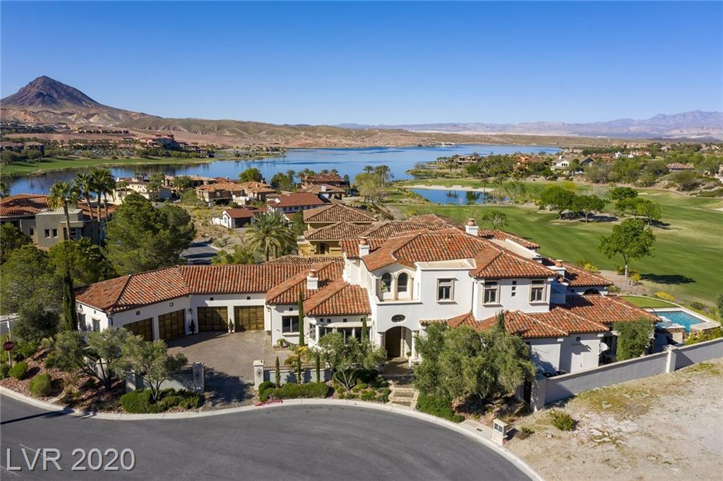 Beautifully designed Mediterranean style home with an open floor plan. Exquisite attention to detail. The architectural design combines warmth, function & elegance. The orientation of the home and covered patios provides outdoor comfort throughout the day and views of the Jack Nicklaus golf course, mountains, & Lake Las Vegas. The oversize kitchen with full-service butler's pantry is its own conversation piece. It features a large island, 2-1/2 ovens, 4 sinks, & 3 refrigerators. Around the corner is a temperature controlled 350 bottle wine closet. The downstairs master is a private retreat with his and her closets. Also, downstairs is a home office with adjoining admin office, large dining & living areas, a large guest en suite & a separate fitness room. Upstairs are 2 en suite bedrooms & a spacious loft w/wet bar; perfect for lounging & recreational activities. Outside is a pool bath w/shower. Dining, shopping, outdoor activities close by. About 30 mins from the Vegas strip.