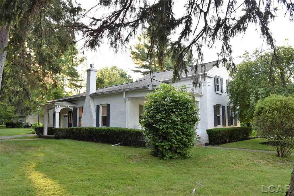 This Beautifully updated  Historic N Scott St home is nestled on 1.07 acres of mature trees and Lovely landscaping. The Large living and dining rooms have new vinyl plank flooring. The living room has a gas log fireplace and access to the covered front porch and side entrance.  The first floor laundry and full bath along with the den  and master bedroom round out the first level. An additional large bedroom on the second floor could be divided into 2 rooms for a third bedroom and  has an adjacent sitting room and full bath. The attached garage is ample sized with front and rear automatic doors. There is an detached single garage for  additional storage a wine cellar style cooler room . There is also an additional outbuilding with workshop and nicely finished office/ Mancave with vaulted ceiling, work station and cabinetry. All the interior updates as well as a new  Furnace, AC, Water heater and updated electrical in the past 2 years.