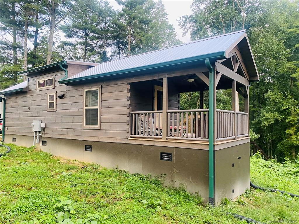Looking for an investment opportunity or thinking of downsizing?  This spacious tiny home cabin is the perfect vacation rental for those looking to vacation in beautiful Western North Carolina and visit Historic Hendersonville and surrounding areas.  This home overlooks beautiful Osceola Lake and offers lake access (private lake). Enjoy the peaceful 1.6 mile level walk around the lake, go for a swim, or test your paddle board skills.  Level easy to maintain .38 acre lot with city water and city sewer.  Enjoy the convenience of city living while only paying county taxes. Home is located close to area golf courses, country clubs, and only 2 miles to Historic Downtown Hendersonville.