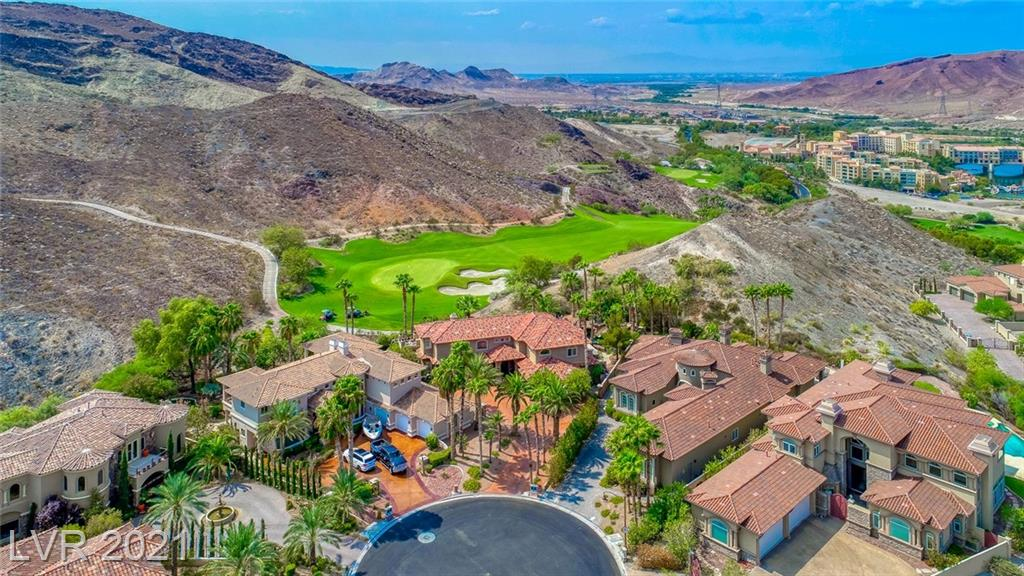 This Exquisite 5 bedroom home sits on the 17th hole of the exclusive SouthShore golf course & features stunning mountain/golf course views.Located in the prestigious guard-gated community of SouthShore in Lake Las Vegas situated in a culdesac with a 3-car garage and extended driveway. The private, lagoon-style pool features rock formations with 4 waterfalls, a waterfall grotto & water slide.Relax by the meditation Zen waterfall pond & fire pit that overlooks the golf course where you will often see long-horned sheep. The main level offers 2 rooms,including a first-floor primary suite and large windowed office.The private upstairs primary bedroom ensuite features a jetted Jacuzzi & large balcony w/ stunning night-time view of the Strip .Additional rooms include a office/den , work out room, balcony overlooking the pool & patio & a spacious loft, theater/game-room. An exceptional home with a floorplan and backyard perfect for entertaining.
