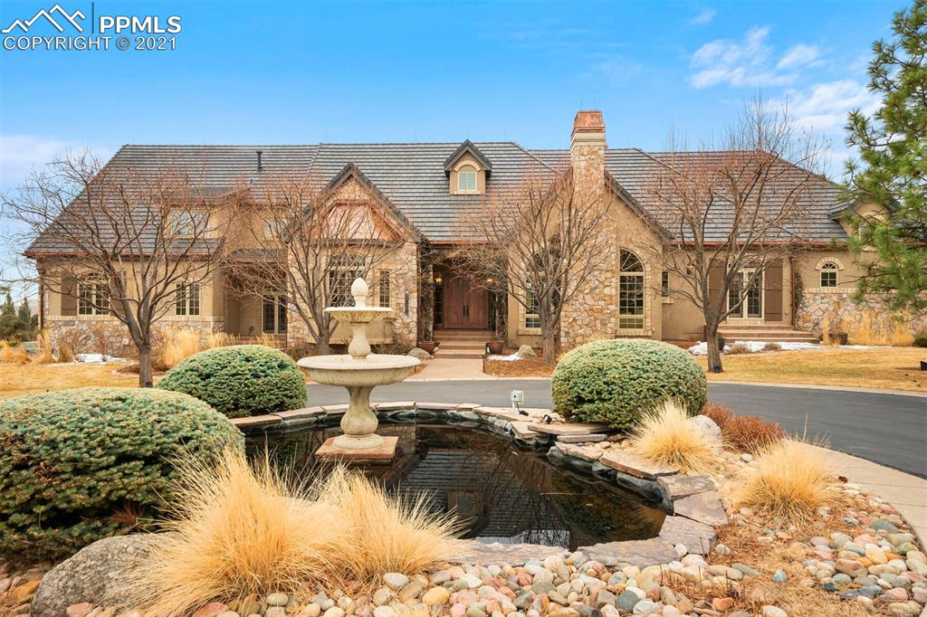 Once inside the gated community of Stratton Preserve, you arrive at this 2.57-acre Country French Estate under the canopy of a tree lined drive to the ivy-covered entry. Step inside, and the outdoors remains yours. This residence wraps around the large veranda, patio & yard with endless windows that take in the majestic Cheyenne Mountain views, while maintaining an intimate privacy. This floor plan allows outdoor access from kitchen, great room and master bedroom to the back yard & Veranda complete with rock stone wall, fireplace, and dining area. Such design creates glorious year-round outdoor gatherings. 