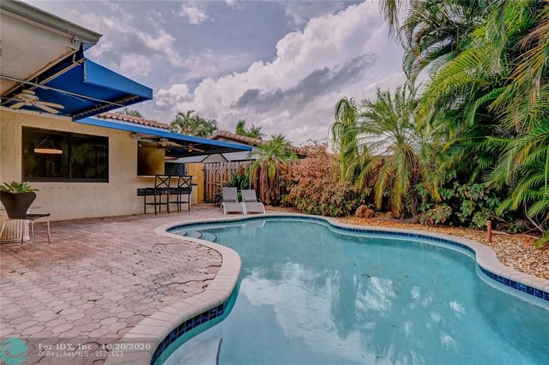 This fantastic house in east Oakland Park features large square footage for a 2 bedroom/2 bath with an open concept living plan.  Easily converted to a 3 bedroom if desired.  Upon entrance, you are greeted by the open living floor plan which combines the living room, Florida room, dining area, and kitchen.  Off the kitchen is a laundry room, additional pantry space and entrance to the 1 car garage.  The house features 2 bedrooms each with an attached bath.  One bedroom is in the rear of the house with an attached bath.  The front bedroom also has an attached bath that is also accessible from the hallway.  Impact windows and doors throughout.  Beautiful pool area with built in BBQ grill connected to natural gas from the street.  The pool has a solar heating system and salt chlorination.