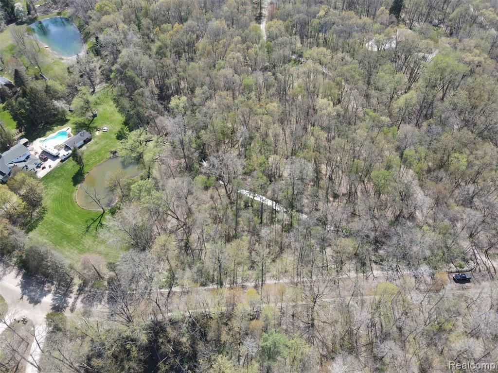 Rare find in Oakland Township to build your DREAM home! Beautiful secluded Natural setting on this secluded 6.3 wooded Acres. Walkout site. Located less than 1 mile from walk and bike entrance to Stoney Creek Metro Park near Baypoint Beach and right next to the newest Oakland Township Park, Stoney Creek Ravine Nature Park. Located within the award-winning Rochester School District (Hugger/Hart/Stoney Creek). Conveniently located close to downtown Rochester and all it has to offer.  Note: Lot adjacent to 2080 East Gunn Road (for searching location).  Wetlands survey completed on parcel and is available, only .02 acres identified as wetlands which is adjacent to Gunn Road - see survey Photo where it is highlighted, no impact to selecting building site.