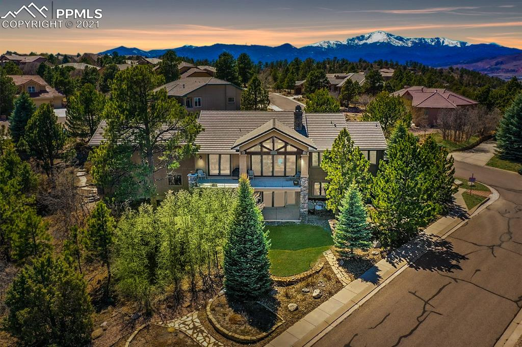 This pristine, four-bedroom, five-bathroom, 6,200 sqft custom-built, rancher is an absolute stunner! With Views that will snatch your breath away and masterfully crafted design accented by carefully detailed features, you will fall in love instantly. Upon entry, you'll be blown away by the tongue & groove, wood, vaulted ceiling accented by wooden beams. Natural hardwood floors run throughout the family room, kitchen, and dining room. From the foyer to the dining room, natural light pours in from the multitude of windows. Keep warm in the family room on cold winter nights with one of the two gas fireplaces in the home. The kitchen is a chef's dream! Dual ovens, granite countertops, gas range oven, coffee bar, two sinks, and natural, oak wood cabinetry! Throw back the double doors and enjoy your main-level, master suite. The five-piece bath features a lovely soaking tub, large shower, two separate vanities, and a vast walk-in closet, complete with built-in storage. The pièce de résistance is the breathtaking views of Colorado Springs from the main-level deck!  The main level also features an office, half-bath, and fully accommodating laundry room, outfitted with cabinets and sink. Venture downstairs to the basement, the ideal location to host your guests, with a wet bar, gas fireplace, walk-out patio, and to top it all off, an in-home movie theatre! Enjoy all your favorite classics or the big game from the comfort of your own leather recliner. Your visitors will never want to leave the comfort of the three large rooms, one of which contains its own private, three-quarter bathroom. Another amazing quality of this stunning home is the extremely spacious home office. This space is the perfect location for an art studio, recording studio, architect room, or renovate into an in-suite apartment with private garage access. Located close to shopping and major roads & I-25, surrounded by trees, and stunning views, this home is the pinnacle of Colorado Springs living!